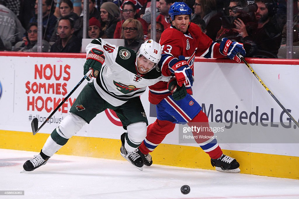 Jason Zucker of the Minnesota Wild and Mike Weaver of the Montreal Canadiens battle for the puck during the NHL game at the Bell Centre on November 8...