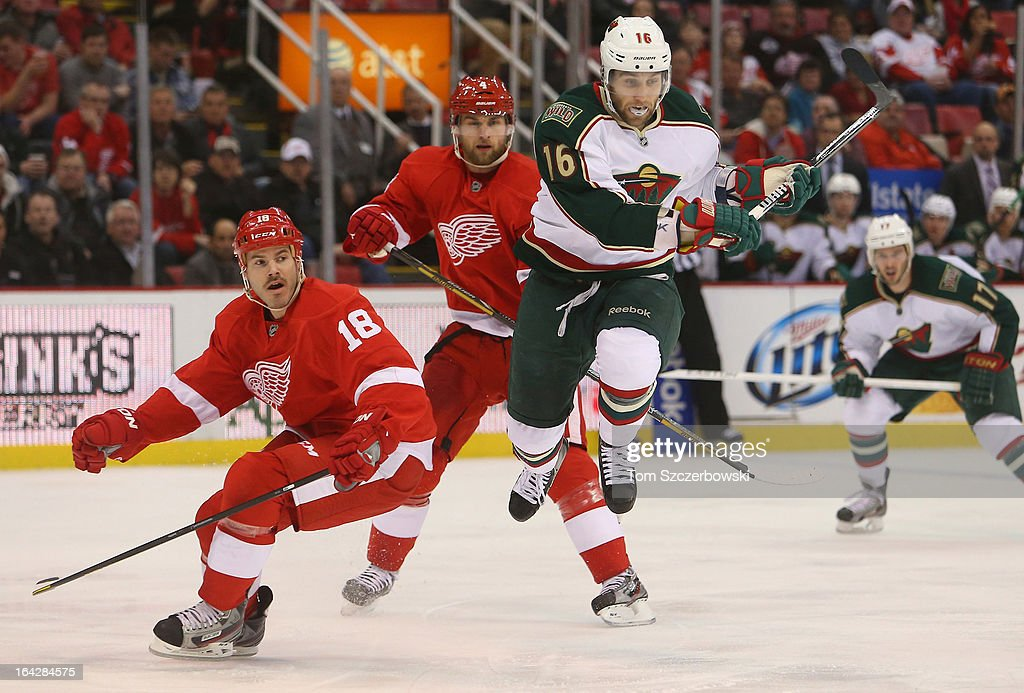 Jason Zucker #16 of the Minnesota Wild avoids Ian White #18 of the Detroit Red Wings at Joe Louis Arena on March 20, 2013 in Detroit, Michigan.