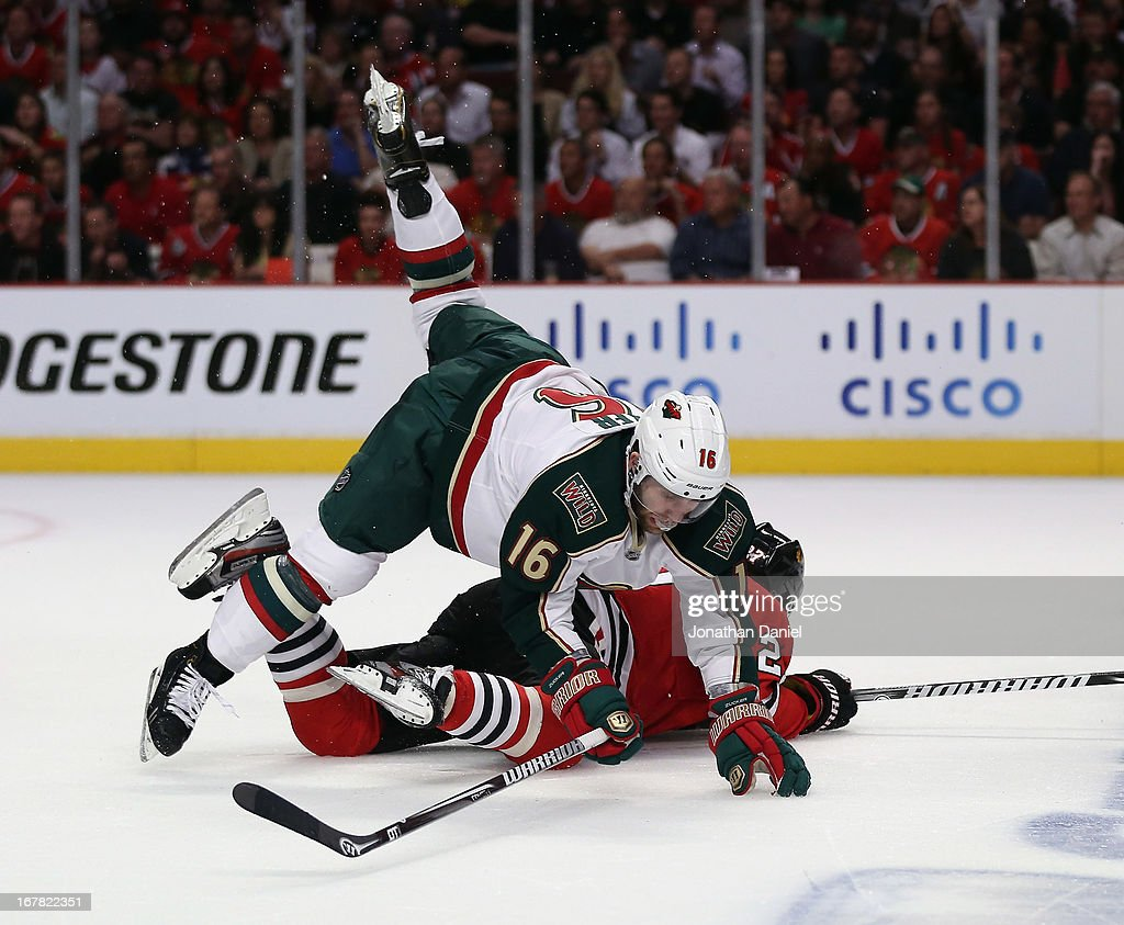 <a gi-track='captionPersonalityLinkClicked' href=/galleries/search?phrase=Jason+Zucker&family=editorial&specificpeople=6670470 ng-click='$event.stopPropagation()'>Jason Zucker</a> #16 of the Minnesota Wild falls over <a gi-track='captionPersonalityLinkClicked' href=/galleries/search?phrase=Johnny+Oduya&family=editorial&specificpeople=3944055 ng-click='$event.stopPropagation()'>Johnny Oduya</a> #27 of the Chicago Blackhawks in Game One of the Western Conference Quarterfinals during the 2013 NHL Stanley Cup Playoffs at the United Center on April 30, 2013 in Chicago, Illinois.