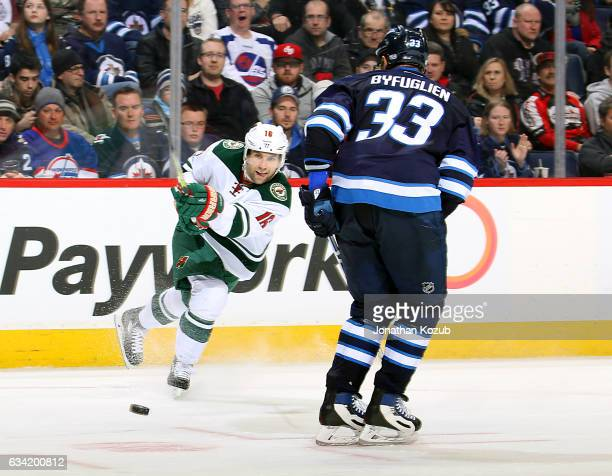 Jason Zucker of the Minnesota Wild shoots the puck past a defending Dustin Byfuglien of the Winnipeg Jets during third period action at the MTS...