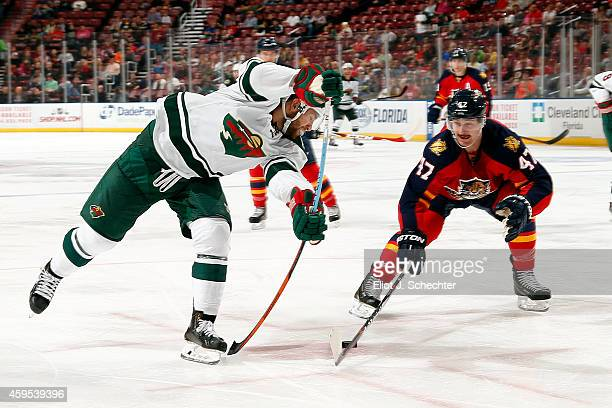 Jason Zucker of the Minnesota Wild tangles with Colby Robak of the Florida Panthers during second period action at the BBT Center on November 24 2014...