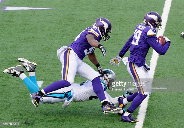 Jasper Brinkley of the Minnesota Vikings helps breakup a tackle attempt by Thomas DeCoud of the Carolina Panthers as Adam Thielen of the Minnesota...