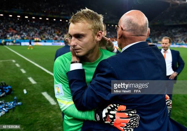 Jasper Cillessen of the Netherlands is consoled by a team staff while walking off the pitch after the defeat in a penalty shootout in the 2014 FIFA...