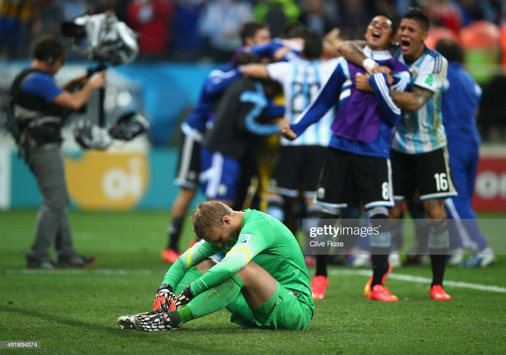 Jasper Cillessen of the Netherlands reacts after being defeated by Argentina in a penalty shootout as Enzo Perez and <a gi-track='captionPersonalityLinkClicked' href=/galleries/search?phrase=Marcos+Rojo&family=editorial&specificpeople=6740047 ng-click='$event.stopPropagation()'>Marcos Rojo</a> of Argentina celebrate during the 2014 FIFA World Cup Brazil Semi Final match between the Netherlands and Argentina at Arena de Sao Paulo on July 9, 2014 in Sao Paulo, Brazil.