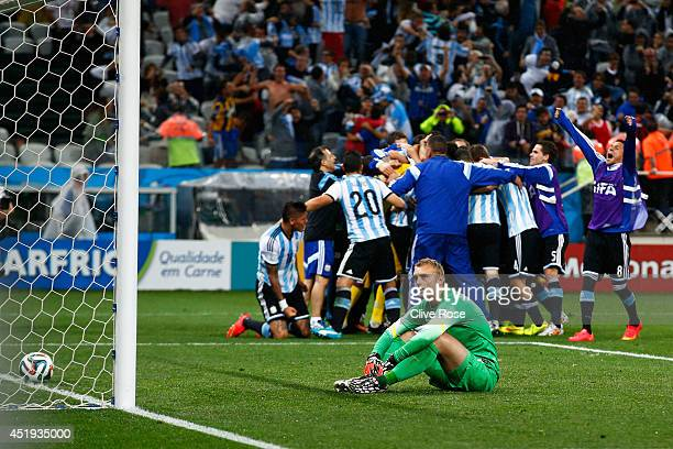 Jasper Cillessen of the Netherlands sits on the pitch after failing to save the penalty kick of Maxi Rodriguez of Argentina as Argentina celebrate...
