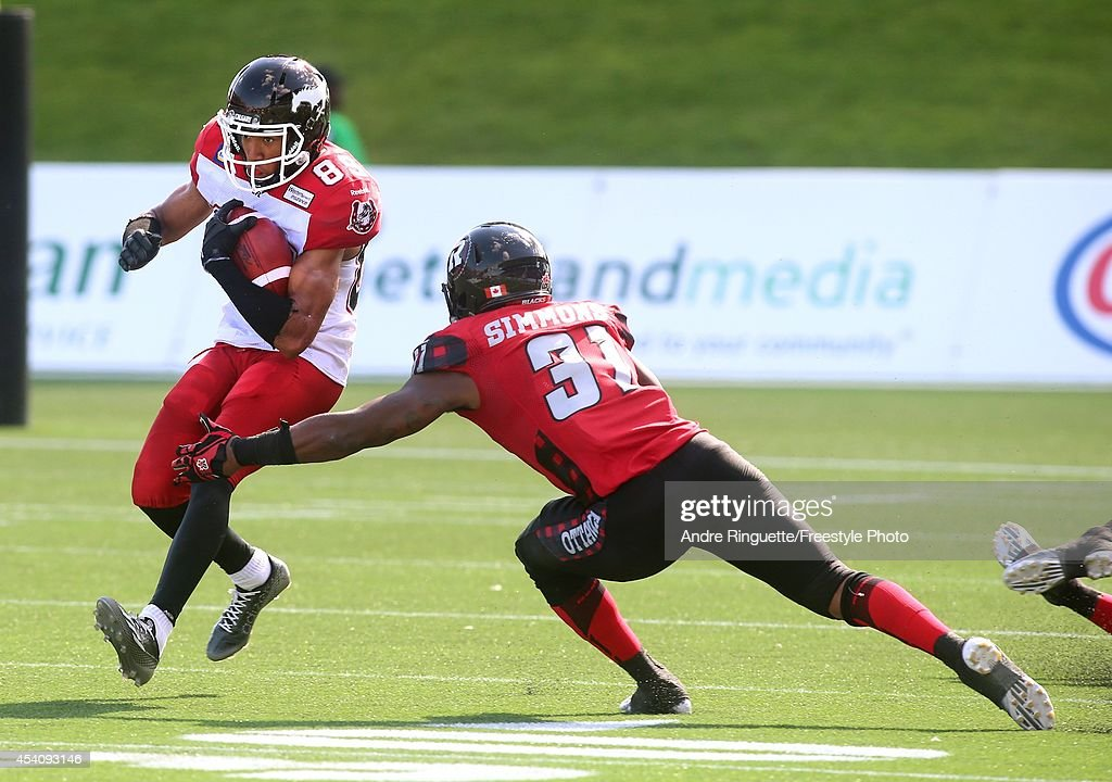 Jasper Simmons #31 of the Ottawa Redblacks reaches to tackle Sederrik Cunningham #89 the Calgary Stampeders on a punt return during a CFL game at TD Place Stadium on August 24, 2014 in Ottawa, Ontario, Canada.
