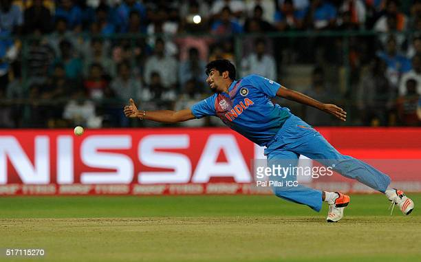 Jasprit Bumrah of India tries to stop a ball of his own bowling during the ICC World Twenty20 India 2016 match between India and Bangladesh at the...