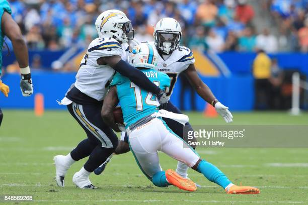 Jatavis Brown of the Los Angeles Chargers tackles Jarvis Landry of the Miami Dolphins during first half at the StubHub Center on September 17 2017 in...