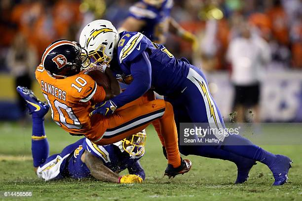 Jatavis Brown of the San Diego Chargers tackles Emmanuel Sanders of the Denver Broncos during the second half of a game at Qualcomm Stadium on...
