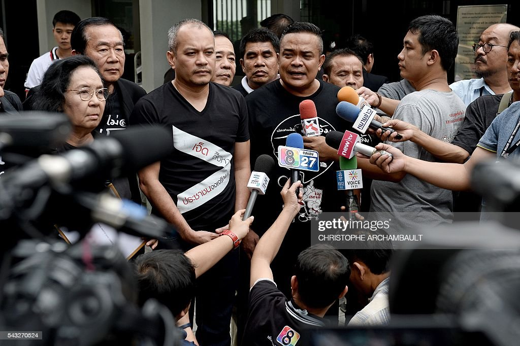 Jatuporn Prompan (C), the leader of Thailand's pro-democracy 'Red Shirt' street movement, answers reporters' questions outside the British Embassy in Bangkok on June 27, 2016. Activists on June 27 urged Britain to hand over details of the multi-million-dollar sale to Thailand of fake bomb detectors that led to the detention of scores of innocent people. British fraudster Gary Bolton was jailed in 2013 for making millions selling the GT200 -- which he billed as a 'magic wand' able to detect tiny particles of explosives or drugs from hundreds of metres away. / AFP / CHRISTOPHE