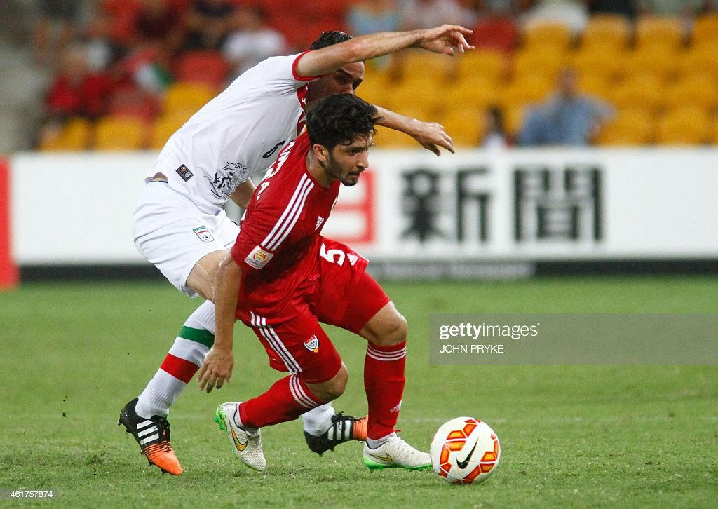 Javad Nekonam (L) of Iran fights for the ball with Amer Abdulrahman of United Arab Emirates during their Group C football match at the AFC Asian Cup in Brisbane on January 19, 2015. AFP PHOTO / John PRYKE