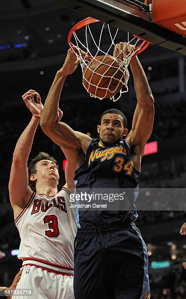 JaVale McGee of the Denver Nuggets dunks the ball over Omer Asik of the Chicago Bulls at the United Center on March 26 2012 in Chicago Illinois NOTE...