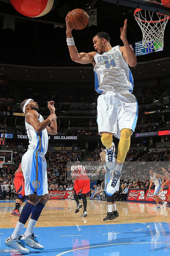 JaVale McGee #34 of the Denver Nuggets grabs a rebound in front of teammate Corey Brewer #13 of the Denver Nuggets as they face the Atlanta Hawks at the Pepsi Center on March 4, 2013 in Denver, Colorado. The Nuggets defeated the Hawks 104-88.