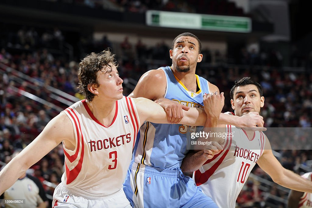 JaVale McGee #34 of the Denver Nuggets, Omer Asik #3 and Carlos Delfino #10 of the Houston Rockets battle for the rebound on January 23, 2013 at the Toyota Center in Houston, Texas.
