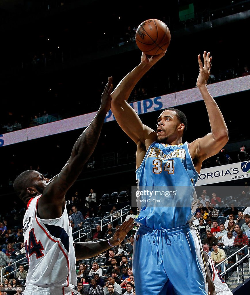 JaVale McGee #34 of the Denver Nuggets shoots against Ivan Johnson #44 of the Atlanta Hawks at Philips Arena on December 5, 2012 in Atlanta, Georgia.