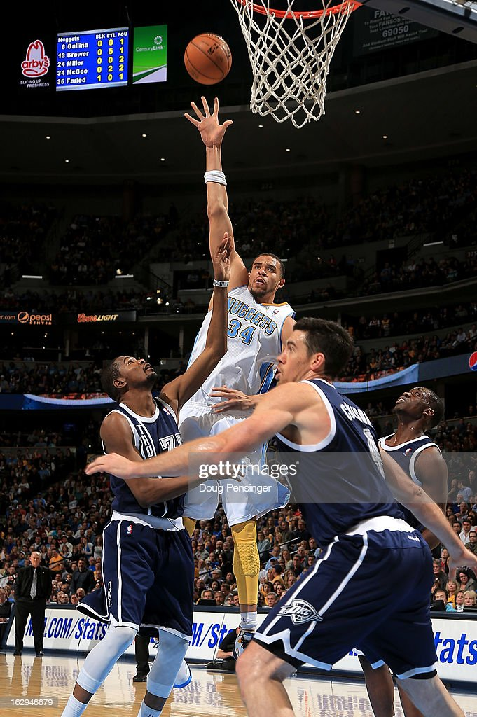 JaVale McGee #34 of the Denver Nuggets takes a shot over Kevin Durant #35 of the Oklahoma City Thunder and Nick Collison #4 of the Oklahoma City Thunder at the Pepsi Center on March 1, 2013 in Denver, Colorado. The Nuggets defeated the Thunder 105-103.