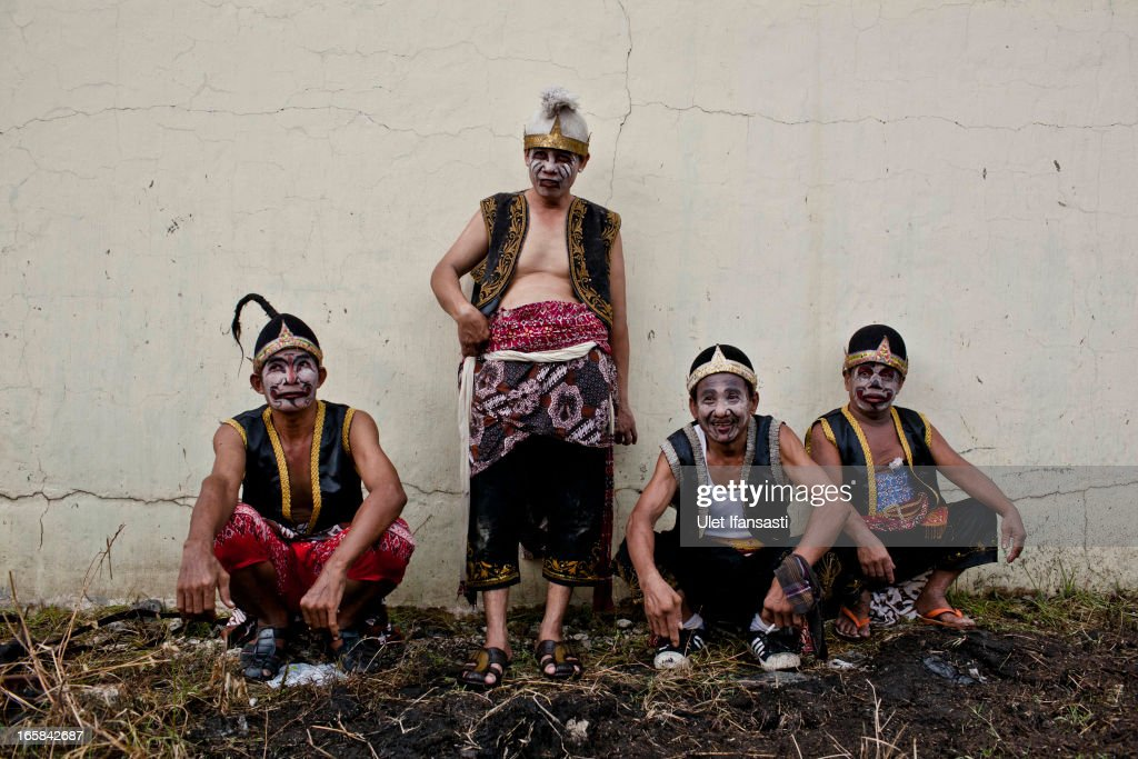 Javanese men wearing traditional costume take a rest during the Cembengan ritual 'Manten Tebu' at Madukismo sugar cane factory on April 6, 2013 in Yogyakarta, Indonesia. The Cembengan ritual, performed to bring about a good season's sugarcane crop, is held annually before the milling and processing season starts in Indonesian sugar mills.