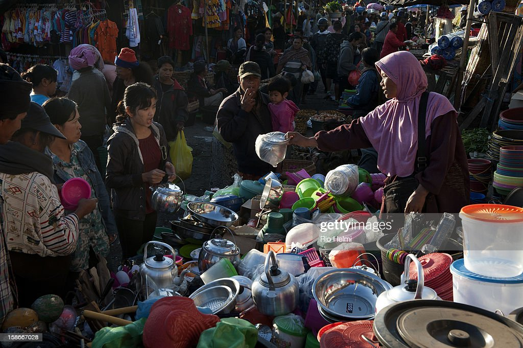 Javanese Muslim woman sells home ware at her stall in the Kintamani market. Cheap homeware, plastic and otherwise, have been flooding into Bali from China for years now..