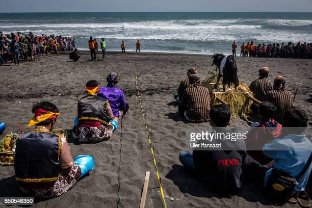 Javanese people pray as they prepare offerings of vegetables and goat before thrown into the sea during the rituals labuhan '1st Suro' during Islamic...