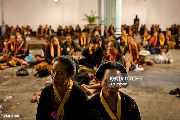 Javanese people sits on yard of Kasunanan Surakarta awaiting the rituals night carnival '1st Suro' during Islamic New Year celebrations at Kasunanan...