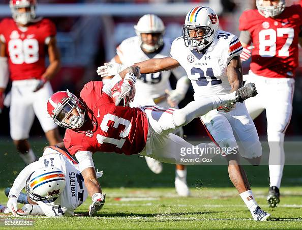 Javaris Davis of the Auburn Tigers defends as ArDarius Stewart of the Alabama Crimson Tide is upended by Stephen Roberts at BryantDenny Stadium on...