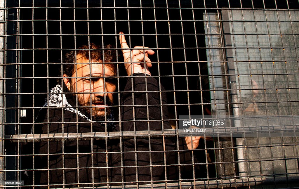 Javed Ahmed Mir, a senior separatist leader of Jammu and Kashmir Libration Front (JKLF) a separatist party fighting politically from Indian and Pakistan for complete Independence of Kashmir, flashes a victory sign from inside an Indian police vehicle after he was detained during a protest on January 04, 2013 in Srinagar, the summer capital of Indian-administered Kashmir, India. JKLF chairman Yasin Malik along with activists and supporters were detained after the group kick-started its 10-day 'jail bharo' to protest against awarding death and life sentences to Kashmiri prisoners by various Indian courts.