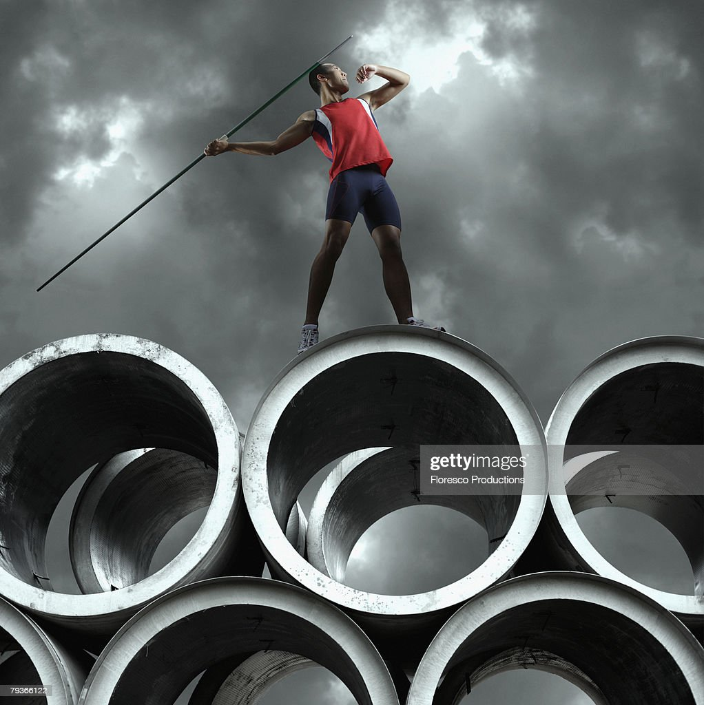 Javelin thrower standing outdoors on large cement cylinders : Stock Photo