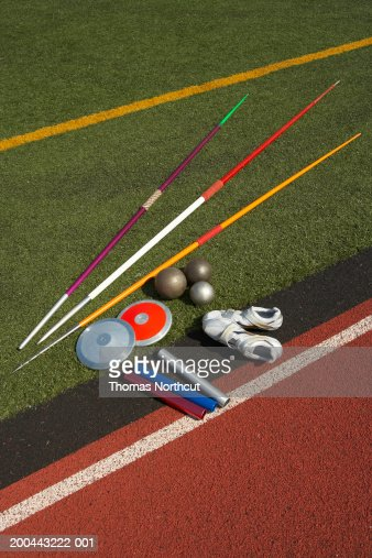 Javelins, discuses, relay batons, shots and sports shoes beside track : Stock Photo