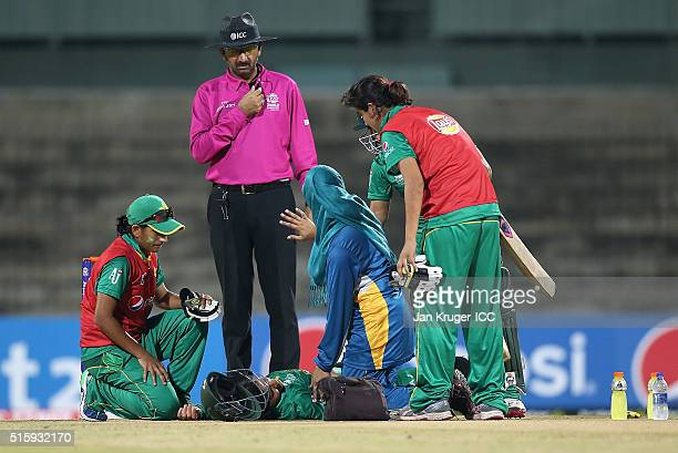 Javeria Khan of Pakistan receives medical help after being struck on the head of the bowling of Shamilia Connell of the West Indies with umpire Anil...