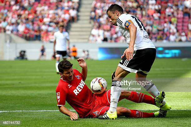 Javi Fuego of Valencia challenges Milos Jojic of Koeln during the Colonia Cup 2015 match between 1 FC Koeln and FC Valencia at RheinEnergieStadion on...
