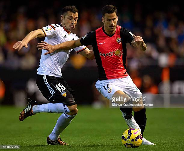 Javi Fuego of Valencia competes for the ball with Edgar Antonio Mendez of Almeria during the La Liga match between Valencia CF and UD Almeria at...