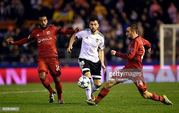 Javi Fuego of Valencia is tackled by Sergi Darder and Alexandre Lacazette of Lyon during the UEFA Champions League Group H match between Valencia CF...
