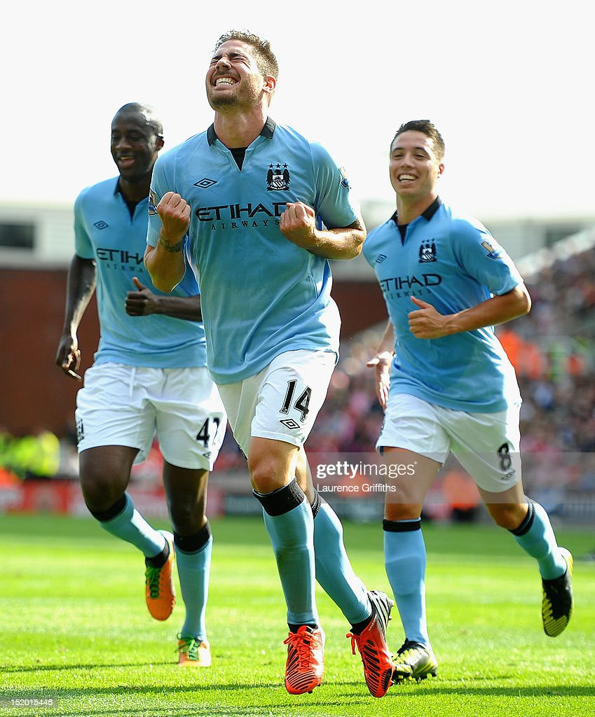 Javi Garcia of Manchester City celebrates scoring the equalising goal followed by Samir Nasri and Yaya Toure during the Barclays Premier League match between Stoke City and Manchester City at Britannia Stadium on September 15, 2012 in Stoke on Trent, England.