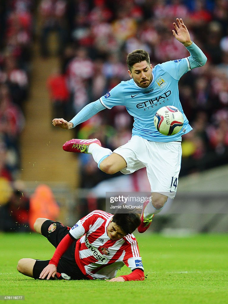 Javi Garcia of Manchester City is tackled by Ki SungYueng of Sunderland during the Capital One Cup Final between Manchester City and Sunderland at...