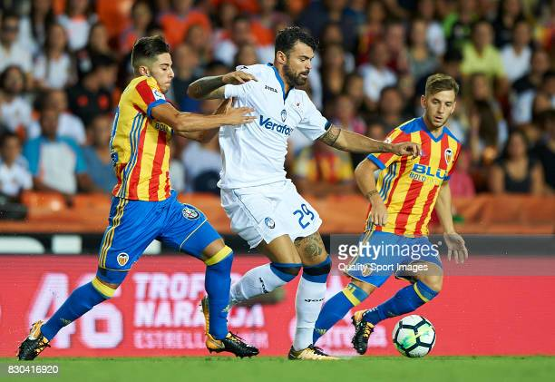 Javi Jimenez and Alvaro Medran of Valencia competes for the ball with Andrea Petagna of Atalanta during the preseason friendly match between Valencia...