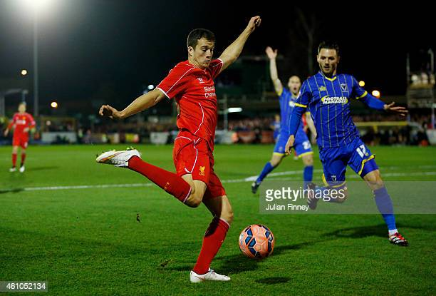 Javi Manquillo of Liverpool croisses the ball as Callum Kennedy of AFC Wimbledon closes in during the FA Cup Third Round match between AFC Wimbledon...