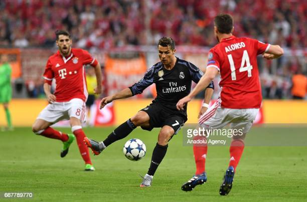 Javi Martinez and Xabi Alonso of Munich and Cristiano Ronaldo of Madrid vie for the ball during the UEFA Champions League quarter final match between...