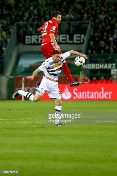 Javi Martinez of Bayern Muenchen and Josip Drmic of Moenchengladbach go up for a header during the Bundesliga match between Borussia Moenchengladbach...