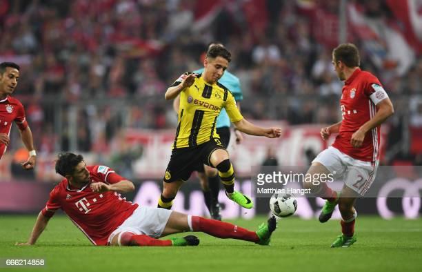 Javi Martinez of Bayern Muenchen tackles Emre Mor of Borussia Dortmund during the Bundesliga match between Bayern Muenchen and Borussia Dortmund at...