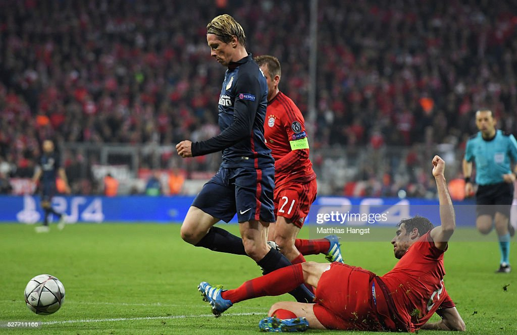 Javi Martinez of Bayern Munich challenges Fernando Torres of Atletico Madrid for a penalty kick during UEFA Champions League semi final second leg match between FC Bayern Muenchen and Club Atletico de Madrid at Allianz Arena on May 3, 2016 in Munich, Germany.