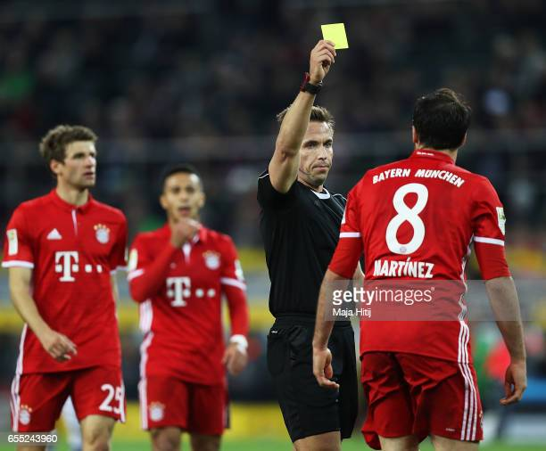 Javi Martinez of Bayern Munich is shown a yellow card by referee Tobias Stieler during the Bundesliga match between Borussia Moenchengladbach and...