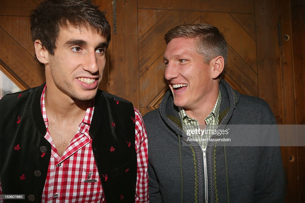Javi Martinez (L) of FC Bayern Muenchen attends with his team mate <a gi-track='captionPersonalityLinkClicked' href=/galleries/search?phrase=Bastian+Schweinsteiger&family=editorial&specificpeople=203122 ng-click='$event.stopPropagation()'>Bastian Schweinsteiger</a> the Oktoberfest beer festival at the Kaefer Wiesnschaenke tent on October 7, 2012 in Munich, Germany.