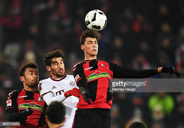 Javi Martínez of Muenchen is challenged by Pascal Stenzel of Freiburg during the Bundesliga match between SC Freiburg and Bayern Muenchen at...
