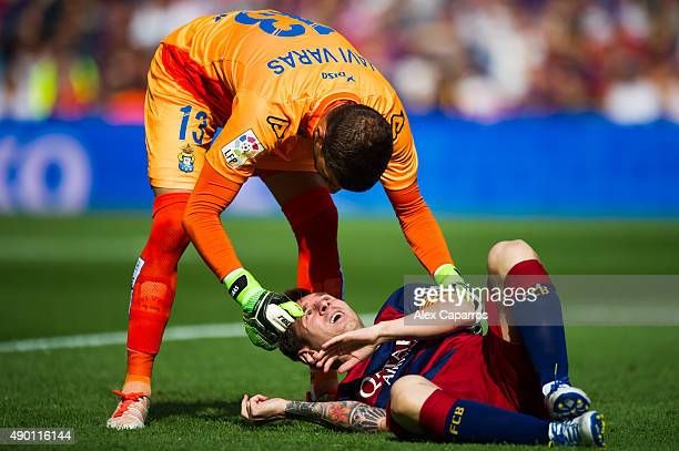 Javi Varas of UD Las Palmas helps Lionel Messi of FC Barcelona as he is injured during the La Liga match between FC Barcelona and UD Las Palmas at...