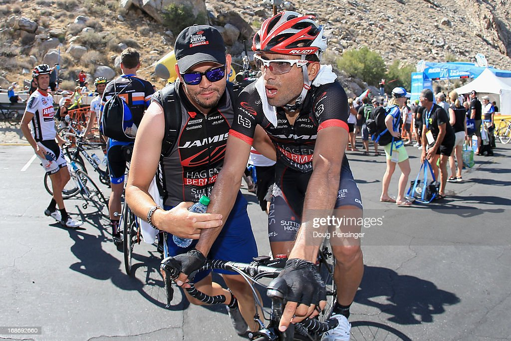 Javier Acevedo of Columbia riding for Jamis-Hagens Berman is escorted away from the finish by his soigneur after he won Stage Two of the 2013 Amgen Tour of California from Murrieta to Palm Springs on May 13, 2013 in Palm Springs, California.