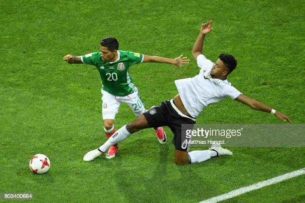 Javier Aquino of Mexico is tackled by Benjamin Henrichs of Germany during the FIFA Confederations Cup Russia 2017 SemiFinal between Germany and...