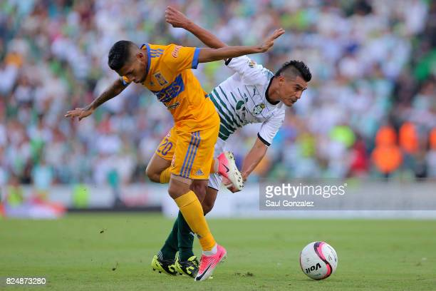 Javier Aquino of Tigres and Osvaldo Martinez of Santos fight for the ball during the 2nd round match between Santos Laguna and Tigres UANL as part of...