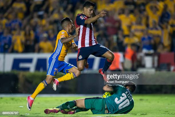 Javier Aquino of Tigres fights for the ball with Jesus Sanchez and Rodolfo Cota of Chivas during the Final first leg match between Tigres UANL and...
