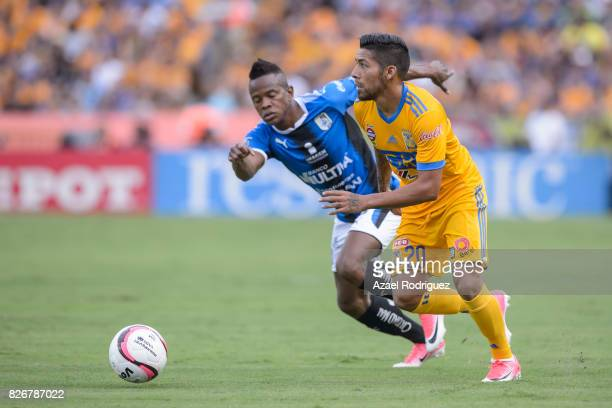 Javier Aquino of Tigres fights for the ball with Yerson Candelo of Queretaro during the 3rd round match between Tigres UANL and Puebla as part of the...