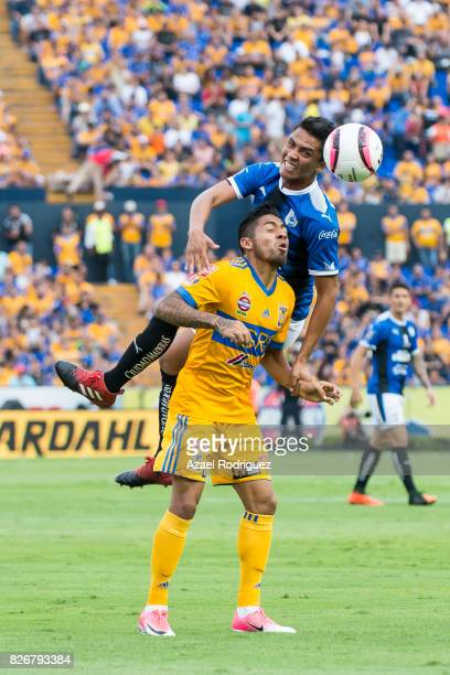Javier Aquino of Tigres goes for a header with Aldo Arellano of Queretaro during the 3rd round match between Tigres UANL and Puebla as part of the...